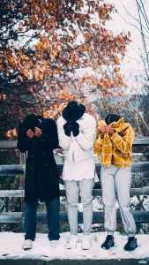 three people covering their faces